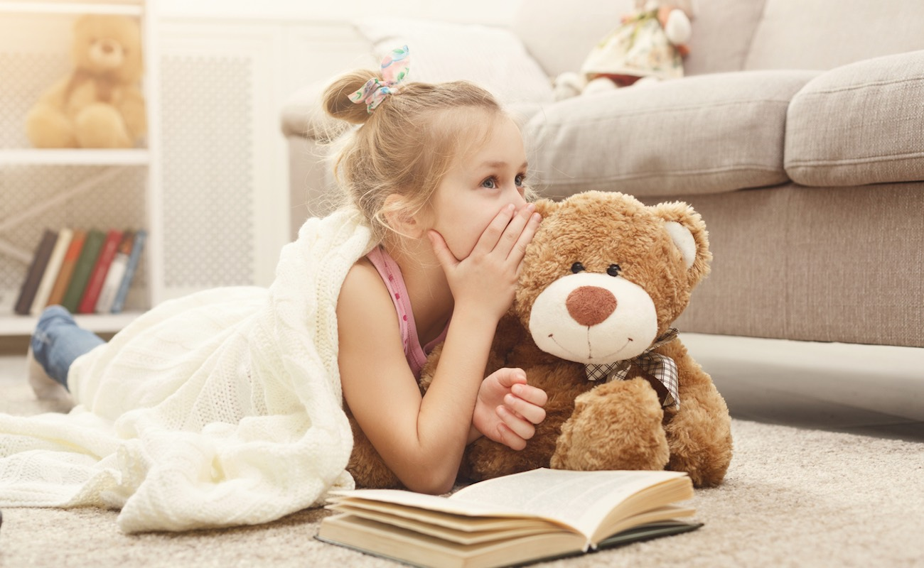 Cute happy little casual girl embracing teddy bear, reading book and sharing secrets with her favorite toy friend. Pretty kid at home, lying on the floor near sofa (Cute happy little casual girl embracing teddy bear, reading book and sharing secrets w